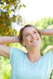 Den lyckliga fundersamma unga kvinnan som ser upp i, parkerar Arkivbild