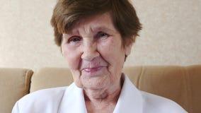 Den lyckliga gamla kvinnan som ler skrattar på kameran, ultrarapid lager videofilmer