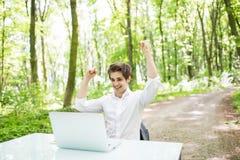 Den lyckliga gick ut affärsmannen med lyftta händer firar upp framgång i jobb eller stor nyheterna framme av bärbara datorn på ko royaltyfri foto