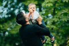 Den lyckliga glade fadern som har gyckel, kastar upp i luften hans småbarn Royaltyfri Foto