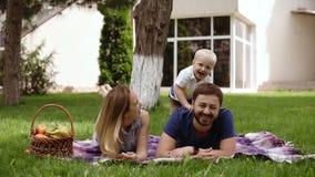 Den lyckliga glade unga familjfadern, modern och den lilla sonen som har rolig det fria som tillsammans spelar i sommar, parkerar lager videofilmer