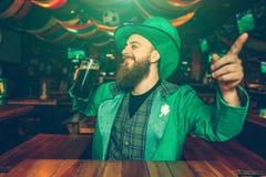 Den lyckliga glade unga mannen sitter på tabellen i bar Han bär gröna Sts Patrick dräkt Grabben pekar framåtriktat royaltyfri fotografi
