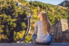 Den lyckliga gladlynta glade turist- kvinnan på den stora väggen av Kina mediterar på semestertur i Asien Flicka som besöker och arkivfoto