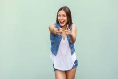 Den lyckliga gladlynta tonårs- flickan med fräknar, kläder för tillfällig stil som ser och pekar, fingrar på kameran inomhus arkivbilder