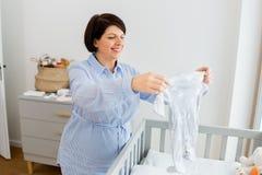 Den lyckliga gravid kvinnainställningen behandla som ett barn kläder hemma fotografering för bildbyråer