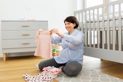 Den lyckliga gravid kvinnainställningen behandla som ett barn kläder hemma royaltyfri foto