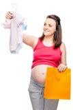 den lyckliga gravida damen väljer kroppen för en pojke eller en flicka på en vit Royaltyfria Bilder