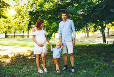Den lyckliga gravida familjen i förväntan av behandla som ett barn Royaltyfri Bild