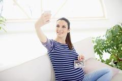 Den lyckliga gravida kvinnan med hennes bild för ultraljudet 3d av henne behandla som ett barn Arkivbilder