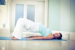 Den lyckliga gravida kvinnan som ligger på golv i bro, poserar Arkivbild