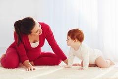 Den lyckliga gravida modern och lilla barnet behandla som ett barn att spela hemma Arkivbilder