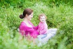 Den lyckliga gravida modern som spelar med henne, behandla som ett barn dottern royaltyfri fotografi