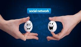 Den lyckliga gruppen av ägg med att le vänder mot att föreställa ett samkväm netto Arkivfoto