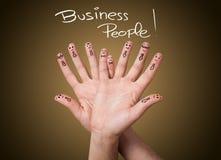 Gruppen av den lyckliga affären fingrar smileys Arkivbild
