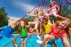 Den lyckliga gruppen av ungar på röda rep i parkerar tillsammans Royaltyfri Foto