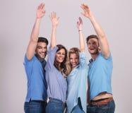 Den lyckliga gruppen av ungdomarsom firar framgång med händer, lyfter Arkivfoto