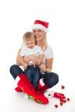 Den lyckliga gulliga familjen i santas hattar fostrar och behandla som ett barn Royaltyfria Bilder