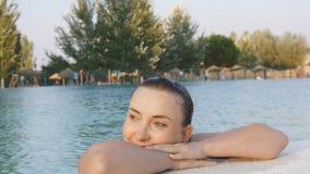 Den lyckliga gulliga kvinnan tycker om vatten på kanten av pölen arkivfilmer
