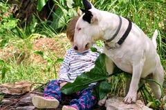 Den lyckliga gulliga kvinnlign behandla som ett barn, och hunden sitter i trädgård Barnet spelar med engelska Bull terrier som de royaltyfri foto
