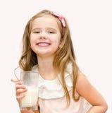 Den lyckliga gulliga lilla flickan med exponeringsglas av mjölkar Royaltyfri Foto
