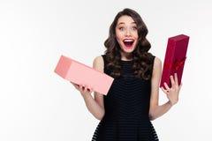 Den lyckliga häpna retro utformade kvinnan med lockigt hår öppnade gåva Arkivbild