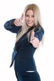 Den lyckliga härliga blonda kvinnan med tummar gör en gest upp över vita lodisar royaltyfri foto