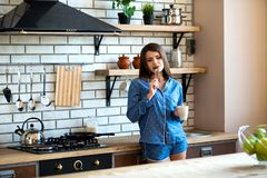 Den lyckliga härliga brunettkvinnan är i köket med en kopp te eller ett kaffe i blå pyjamas Ottalöneförhöjningen är en bra vana arkivbild