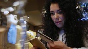 Den lyckliga härliga flickan med lockigt hår i en restaurang shoppar direktanslutet stock video