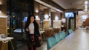 Den lyckliga härliga flickan med lockigt hår kommer i en restaurang stock video