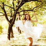 Den lyckliga härliga ljust rödbrun flickan dansar i en flygvittappning Arkivfoto