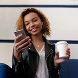 Den lyckliga härliga mörkhyade flickan ser in i telefonen, medan sitta på en blå soffa i det väntande rummet eller i ett kafé En  royaltyfria bilder