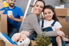 Den lyckliga härliga modern kramar den lilla dottern, medan fadern väljer målarfärg för att måla väggen royaltyfria bilder