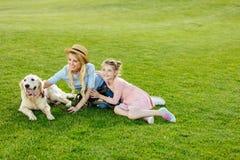 den lyckliga härliga modern och dottern med golden retriever dog sammanträde på grön gräsmatta royaltyfri fotografi