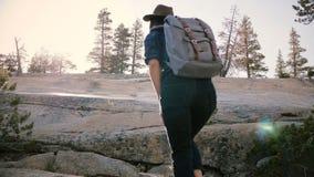 Den lyckliga härliga turist- flickan med ryggsäcken som fotvandrar på stort, vaggar undersökande solig ultrarapid för den Yosemit arkivfilmer