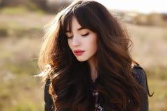 Den lyckliga härliga unga kvinnan med långt svart sunt hår tycker om ljust utomhus- för ny luft och för sol på solnedgången Royaltyfri Foto