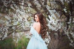 Den lyckliga härliga unga kvinnan med långt svart sunt hår tycker om nya blommor, och solljus i blomning parkerar på solnedgången Royaltyfri Bild