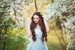 Den lyckliga härliga unga kvinnan med långt svart sunt hår tycker om nya blommor, och solljus i blomning parkerar på solnedgången Royaltyfri Fotografi