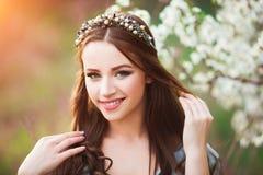 Den lyckliga härliga unga kvinnan med långt svart sunt hår tycker om nya blommor, och solljus i blomning parkerar på solnedgången Royaltyfri Foto