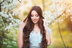 Den lyckliga härliga unga kvinnan med långt svart sunt hår tycker om nya blommor, och solljus i blomning parkerar på solnedgången Fotografering för Bildbyråer