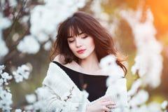 Den lyckliga härliga unga kvinnan med långt svart sunt hår tycker om nya blommor, och solljus i blomning parkerar på solnedgången Arkivfoto