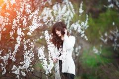 Den lyckliga härliga unga kvinnan med långt svart sunt hår tycker om nya blommor, och solljus i blomning parkerar på solnedgången Arkivbild