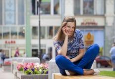 Den lyckliga härliga unga kvinnan sitter på en bänk arkivfoton