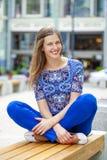 Den lyckliga härliga unga kvinnan sitter på en bänk arkivfoto