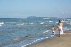 Den lyckliga härliga unga mamman och barnet som promenerar havet, sätter på land, vågor och vind royaltyfria bilder