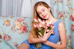 Den lyckliga härliga unga spensliga flickan sitter på en soffa i en coz royaltyfria bilder