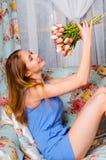 Den lyckliga härliga unga spensliga flickan sitter på en soffa i en coz arkivfoto