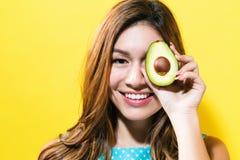 Den lyckliga hållande avokadot för den unga kvinnan halverar Fotografering för Bildbyråer