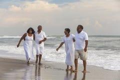 Den lyckliga höga afrikanska amerikanen kopplar ihop mankvinnor på stranden arkivbild