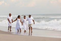 Den lyckliga höga afrikanska amerikanen kopplar ihop mankvinnor på stranden arkivfoton
