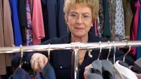 Den lyckliga höga blonda kvinnan i exponeringsglas shoppar välja en blus i ett bekläda lager stock video